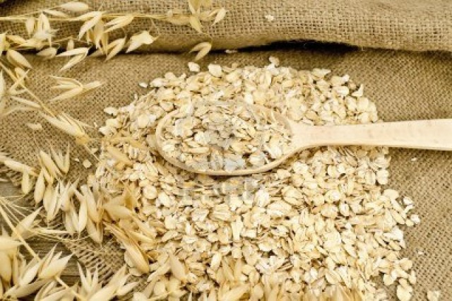 oat-flakes-with-a-wooden-spoon-stalks-of-oats-on-sacking-and-wooden-board